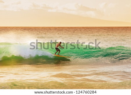 Surfer on Beautiful Wave at Sunset - stock photo