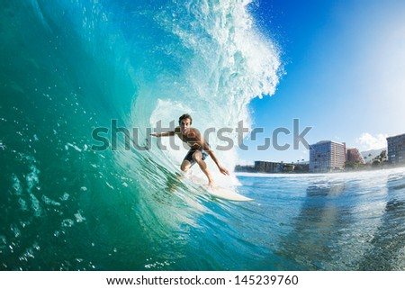 Surfer on Blue Ocean Wave Getting Barreled - stock photo