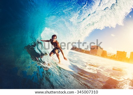 Surfer on Blue Ocean Wave Getting Barreled at Sunrise - stock photo