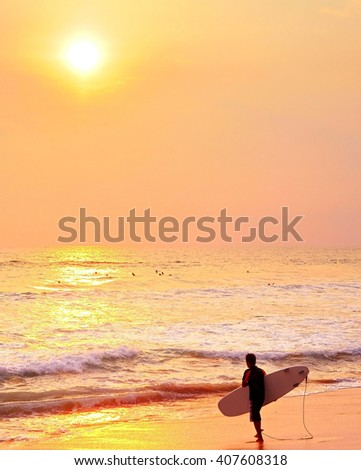 Surfer on ocean beach ready for surfing at sunset.