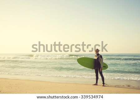 Surfer on the beach holding is surfboaerd and watching the waves - stock photo