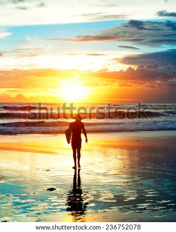 Surfer on the beach in sunset light. Bali island, Indonesia