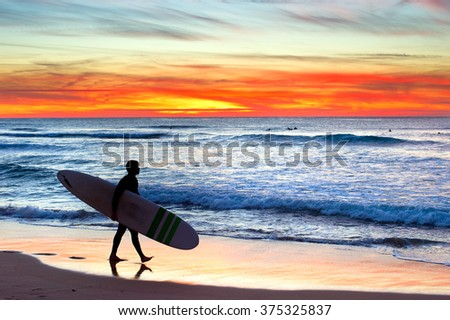 Surfer on the ocean beach at colorful sunset. Portugal