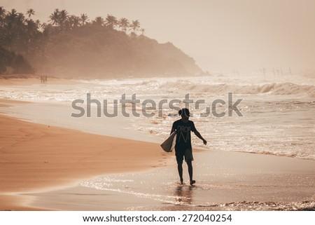 Surfer on the sunrise - stock photo