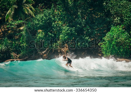 Surfer on the wave in the tropic country - stock photo
