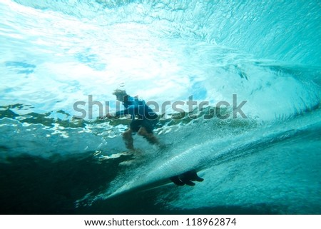 Surfer on tropical wave underwater vision - stock photo