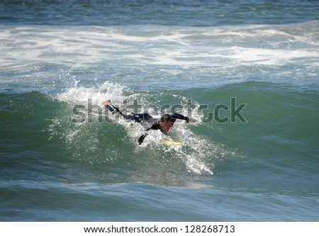 Surfer paddling to catch a wave in California.
