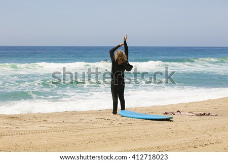 Surfer putting on a wetsuit on the beach
