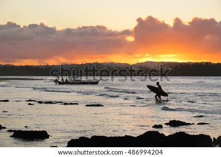 Surfer returning to the beach at sunset