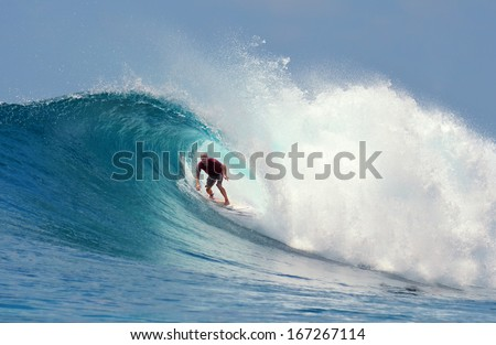 Surfer rides a large blue tropical wave - stock photo