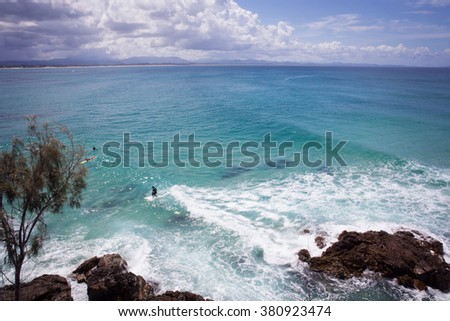 Surfer rides a wave in a turquoise bay under Australian sky - stock photo