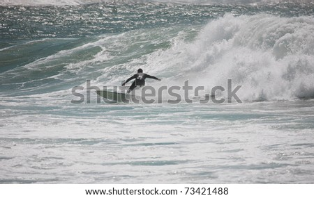 surfer rides a wave in ericeira beach - stock photo