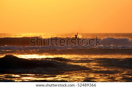Surfer rides waves at sunset, Bali, Indonesia - stock photo