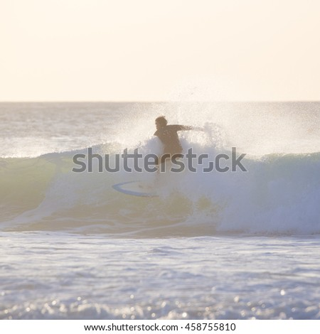 Surfer riding a powerful wave. Square composition.