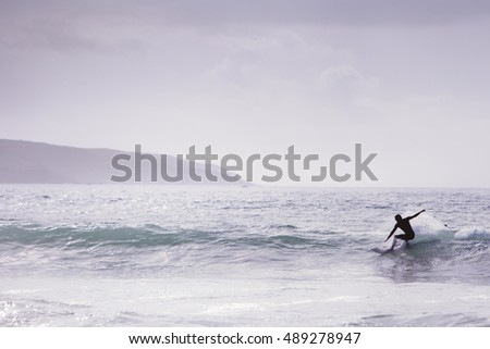 Surfer riding a wave, wearing a wetsuit at godrevy beach in cornwall uk. Do not have model release but face has been  darken and used the liquefy tool in photoshop to change the features of the face.
