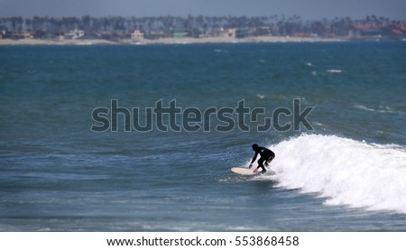 Surfer riding a white wave towards the shore.