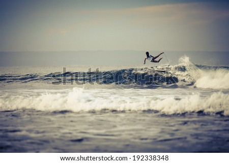 Surfer riding large  ocean wave in the day time