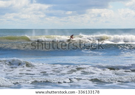 Surfer riding the waves on the east coast of Florida, USA. - stock photo