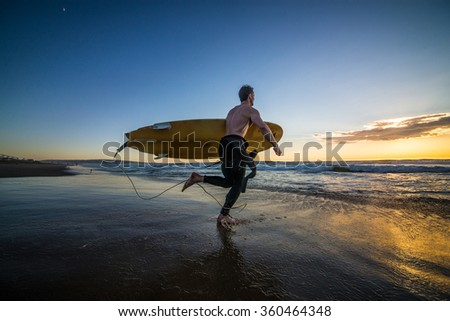 Surfer running into water with surf board at sunset - stock photo