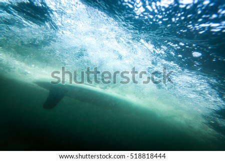 surfer seen from underwater, moving at high speed with a lot of air bubbles