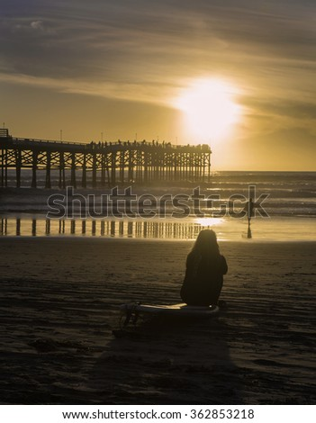 surfer silhouettes at sunset - stock photo