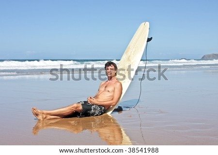 Surfer sitting against his surfboard at the beach after surfing - stock photo