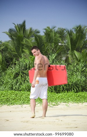 Surfer standing on the beach. - stock photo
