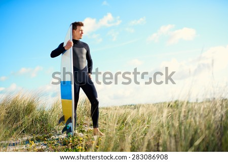 Surfer standing on top of a sand-dune in his wetsuit holding his surfboard upright alongside him as he stares into the distance in evening light with copyspace - stock photo