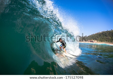 Surfer Surfing Inside Blue  Surfer tube rides inside hollow crashing wave over shallow reef.Swimming water perspective of sport. - stock photo