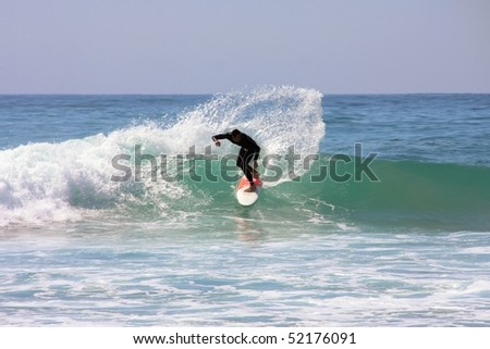 Surfer surfing the waves at the atlantic ocean - stock photo
