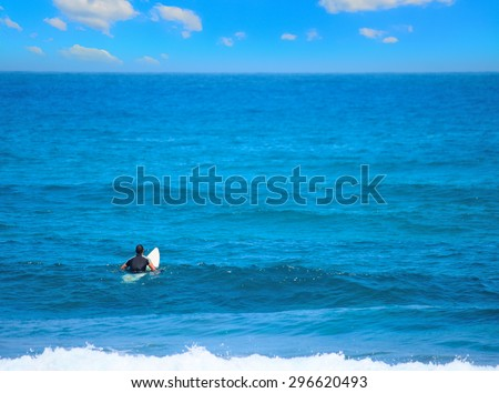 surfer waiting for the wave under a huge cloud