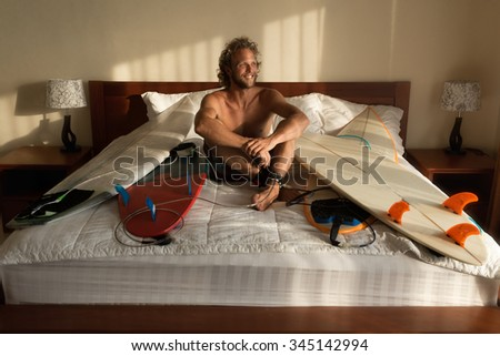 Surfer wake-up with his boards in bed - stock photo