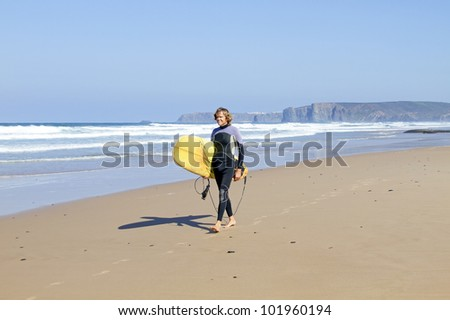 Surfer walking along the beach with his surfboard - stock photo