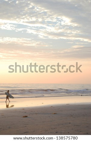 surfer walking in the sunset - stock photo