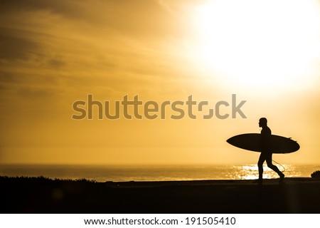 Surfer walking in the sunset in Santa Cruz, California - stock photo