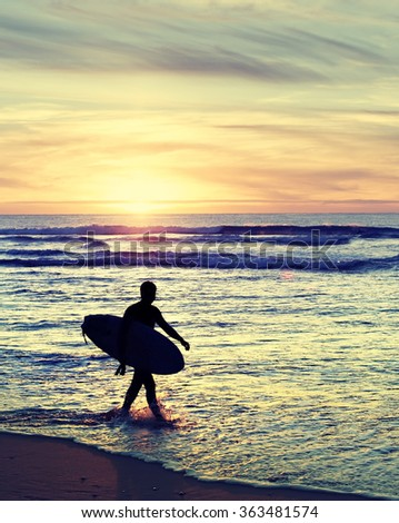 Surfer walking on the beach at sunset. Vintage color - stock photo