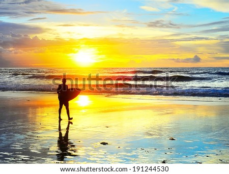 Surfer walking with surfboard on the ocean beach at sunset. Bali island, Indonesia