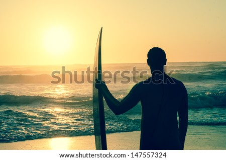 Surfer watching the waves at sunset in Portugal. - stock photo