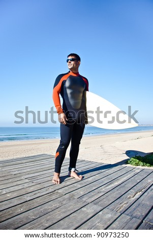 Surfer wearing a long wetsuit holding his surf board. - stock photo