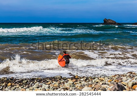 Surfer with a surfboard goes to Atlantic ocean with waves on coast or shore stone beach - stock photo