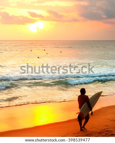 Surfer with a surfboard on the beach at sunset. Sri Lanka