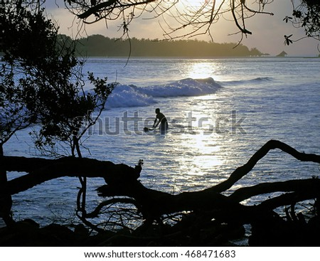 Surfer with board on the waves of the ocean off the coast of