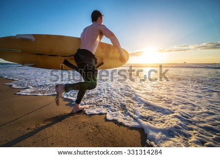 Surfer with board running into the the ocean at sunset - Sportive man going to surf on a tropical beach - stock photo