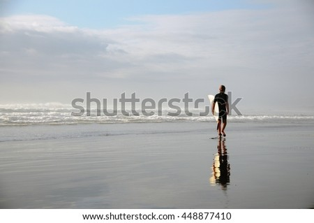 Surfer with board walking along the ocean in Muriwai Beach Auckland - stock photo