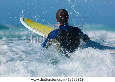 Surfer with his board in the waves entering the sea