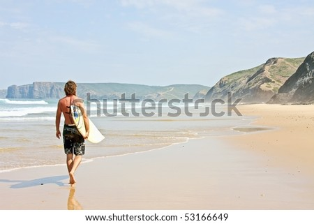 Surfer with his surfboard walking along the beach - stock photo