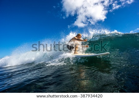 Surfer with long white hair rides in the big ocean wave in Mauritius Island, Indian Ocean