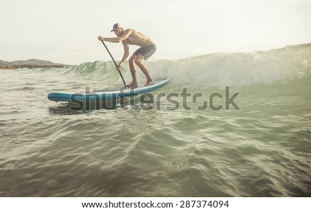 surfer with paddle board catching the wave. concept about sport and people - stock photo
