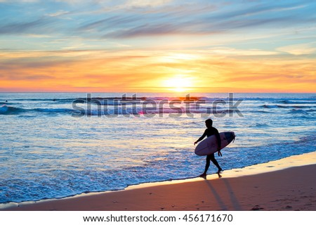 Surfer with surfboard on the ocean beach at sunset.
