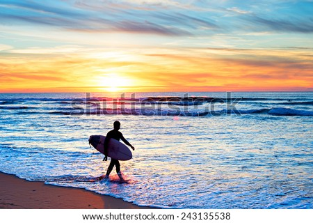 Surfer with surfboard walking on the beach at sunset - stock photo